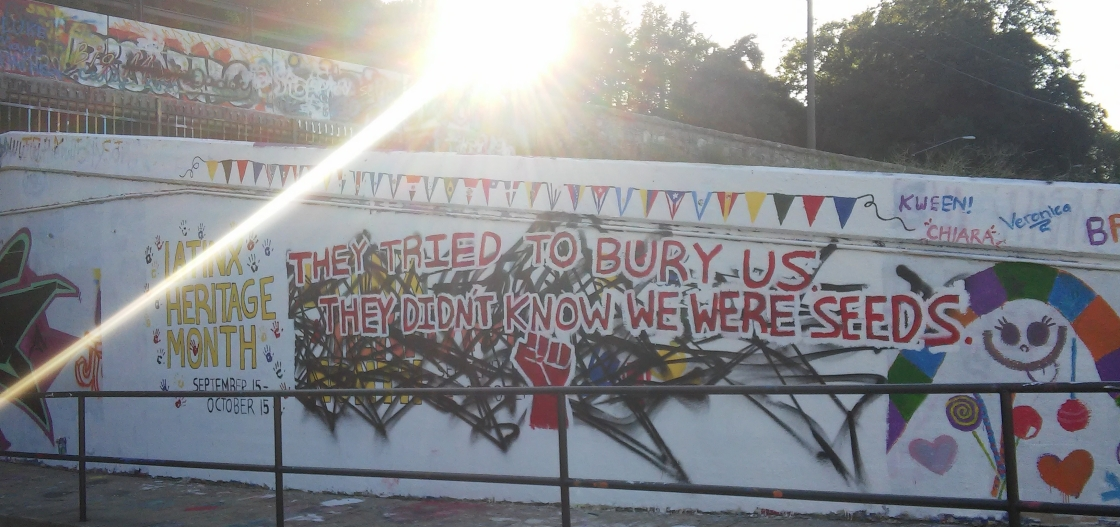 "A vandalized mural for LatinX Heritage Month that has been repainted by its creators to read ""They tried to bury us, they didn't know we were seeds"" with a raised fist."